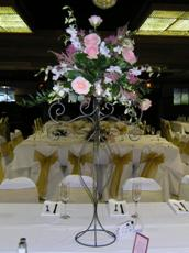 Picture of 5-Arm Iron Candelabra with Votive Cups (Wedding Rental), Holding an Arrangement of Erica Dendrobium Orchids, Esperance Roses, Pink Asilbe, Pink Menarda, Salal Leaves, and Italian Ruscus